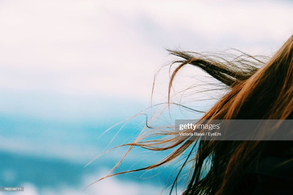 Close-Up Of The Hair Of A Young Woman Against Sky : Stock Photo