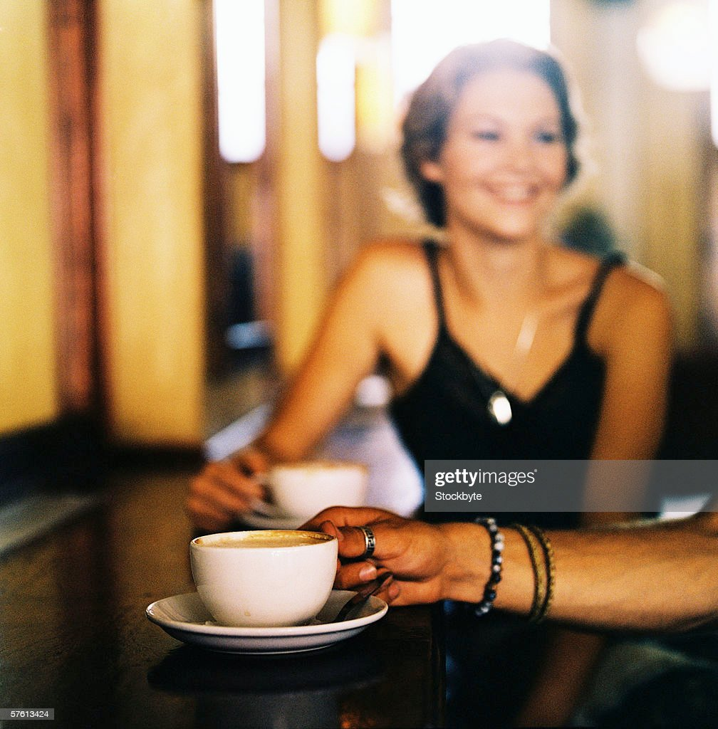 Close-up of the hand of a man picking up a cup of coffee : Stock Photo