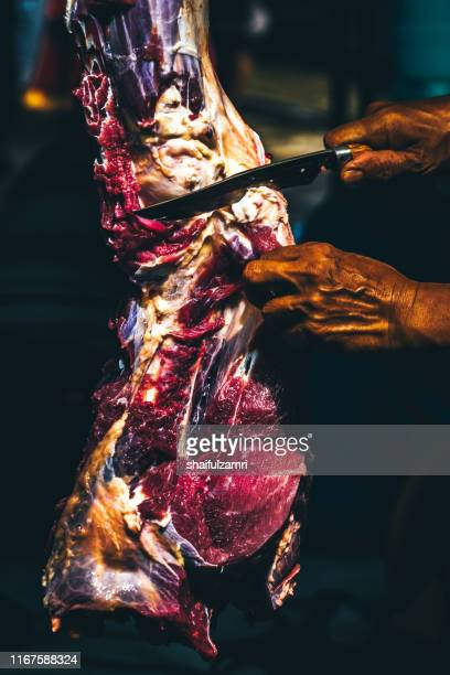 closeup of the hands of a butcher cutting slices of raw meat off a large loin. - shaifulzamri 個照片及圖片檔