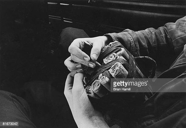 Closeup of the hands of an unidentified IRA member who inserts a detonator into a homemade gelignite bomb Derry Northern Ireland May 3 1972