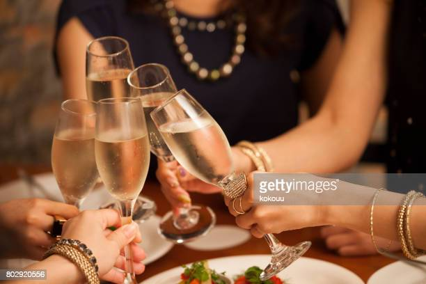 close-up of the hands of the girls making a toast. - christmas party stock photos and pictures