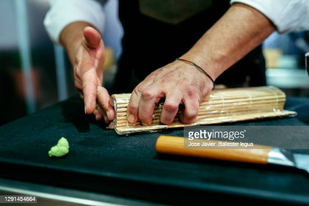 close-up of the hands of the western master chef itamae covering a roll of bluefin tuna loin maki on a kitchen table with the mat. - nigiri stock pictures, royalty-free photos & images