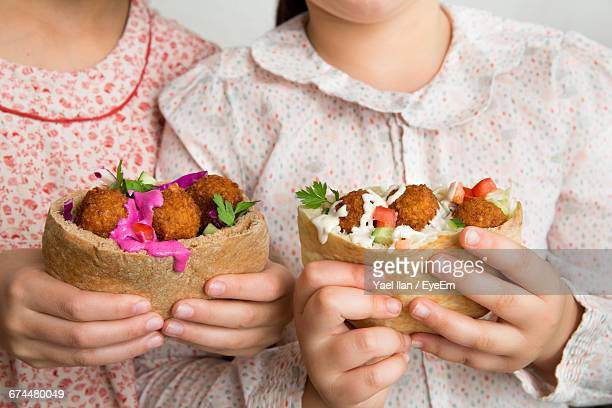 Close-Up Of The Hands Of Two Girls Holding Falafel Sandwiches