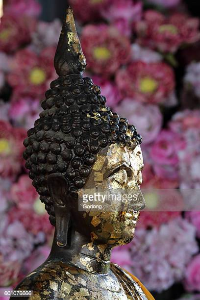 Closeup of the head of a statue of the Buddha covered in gold leaf Wat Pho Bangkok Thailand