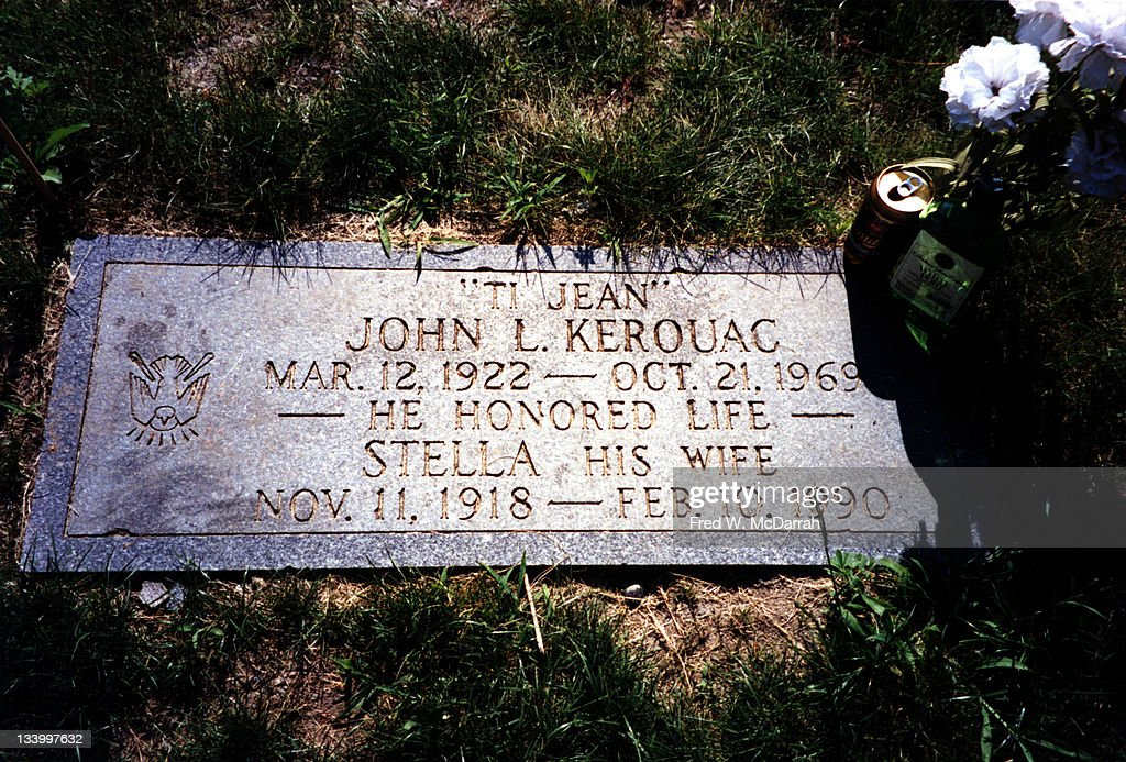 Close-up of the headstone at the grave of American author Jack Kerouac and his wife, Stella, Lowell, Massachussets, June 21, 1995. The stone reads 'Ti Jean; John L. Kerouac, Mar. 12, 1922 - Oct. 21, 1969; He Honored Life; Stella, His Wife, Nov. 11, 1918 - Feb. 10, 1990.' Offerings left at the grave include flowers, an open can of Miller beer, and a bottle of port.