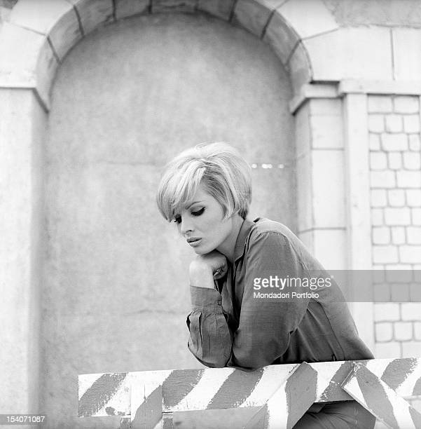 Close-up of the Italian actress Scilla Gabel, born Gianfranca Gabellini, leant against a wood barrier, with her eyes looking downward. Italy, 1965.