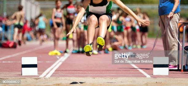 Close-up of the legs of a girl flying on the sand in long jump