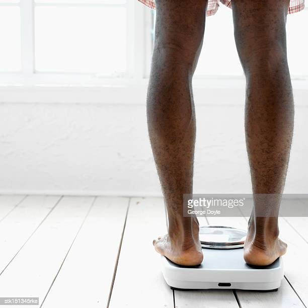 close-up of the legs of a young man standing on a weighing scales - low section stock pictures, royalty-free photos & images
