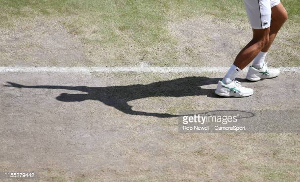 A closeup of the shadow Novak Djokovic during his match against Roberto Bautista Agut in their Gentleman's Singles SemiFinal match during Day 11 of...