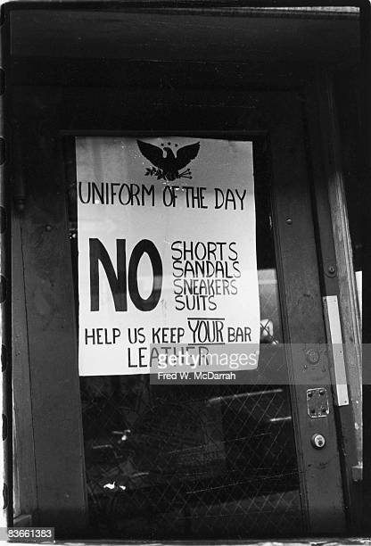 Closeup of the sign on the door of the Eagle Tavern that lists the dress code August 31 1971 The sign reads 'Uniform of the Day No Shorts Sandals...