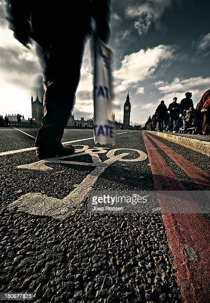 Closeup of the street on Westminster Bridge in London. A tourist is walking by hloding a modern tate museum bag, In the background the Big Ben clock...