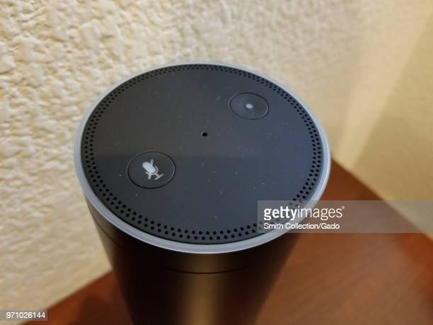 Closeup of the top of an Amazon Echo smart speaker using the Alexa service on a light wooden surface in a suburban home setting San Ramon California...