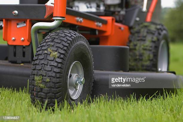 Close-up of the wheels and base of a working lawn mower