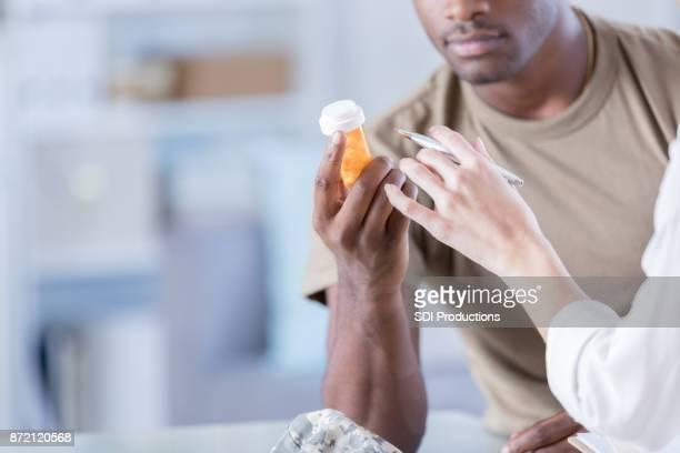 Closeup of therapist giving military patient prescription medication