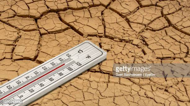 close-up of thermometer on barren land - heat stock pictures, royalty-free photos & images