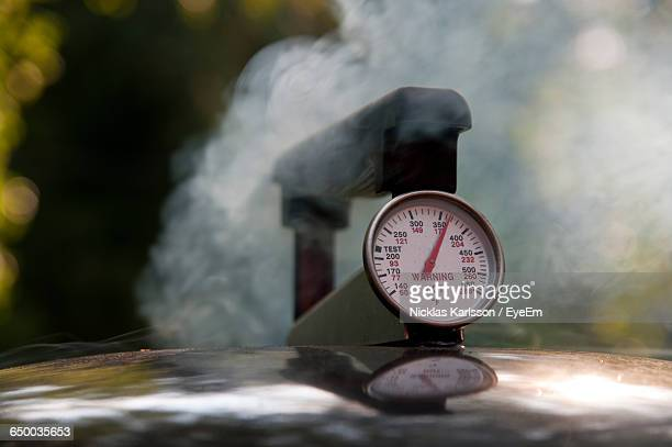 Close-Up Of Thermometer On Cooking Utensil With Steam In Back Yard