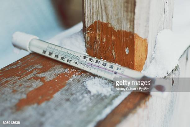 Close-Up Of Thermometer On Wooden Railing During Winter
