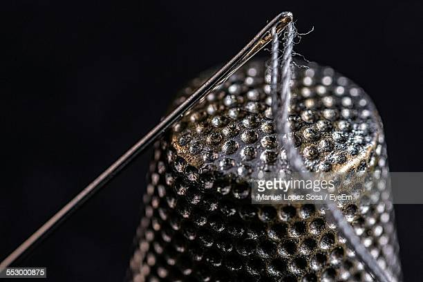 close-up of thimble and thread in needle against black background - thimble stock photos and pictures