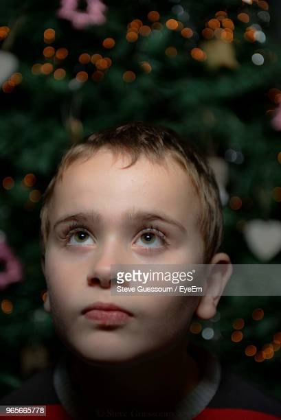 Close-Up Of Thoughtful Boy Against Christmas Tree