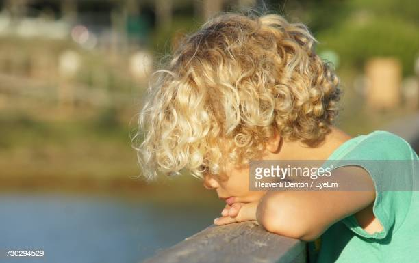 Close-Up Of Thoughtful Boy Leaning On Railing
