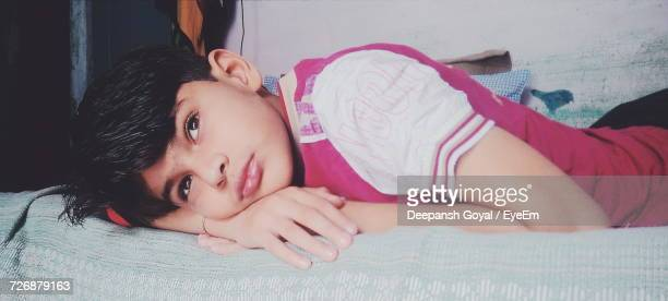 Close-Up Of Thoughtful Boy Looking Away While Lying On Bed