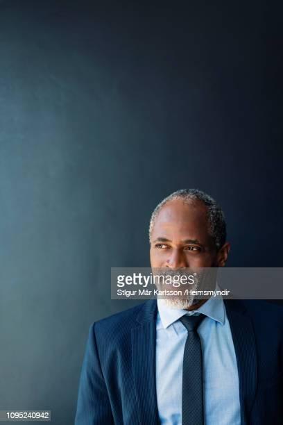 primo piano di uomo d'affari premuroso contro muro - completo nero foto e immagini stock