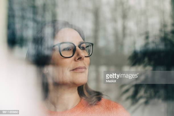 close-up of thoughtful businesswoman wearing eyeglasses seen through window - photographed through window stock pictures, royalty-free photos & images