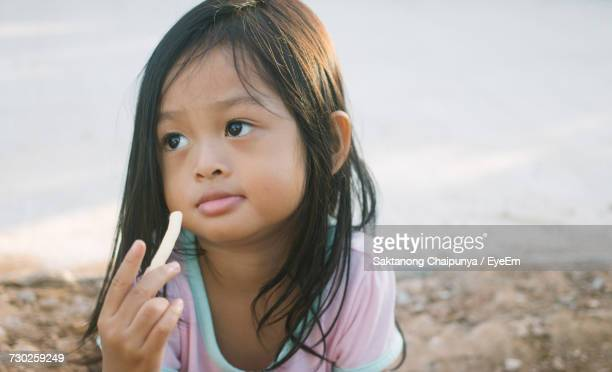 Close-Up Of Thoughtful Girl Holding Food At Beach