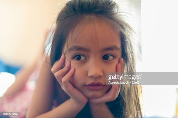 Close-Up Of Thoughtful Girl Leaning On Elbows At Home
