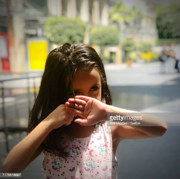 close-up of thoughtful girl standing in city - concepts & topics stock pictures, royalty-free photos & images
