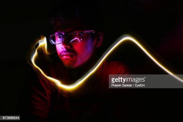close-up of thoughtful man by light trail in darkroom - light trail stock photos and pictures