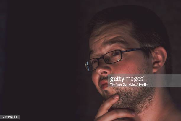 Close-Up Of Thoughtful Man Looking Away In Darkroom