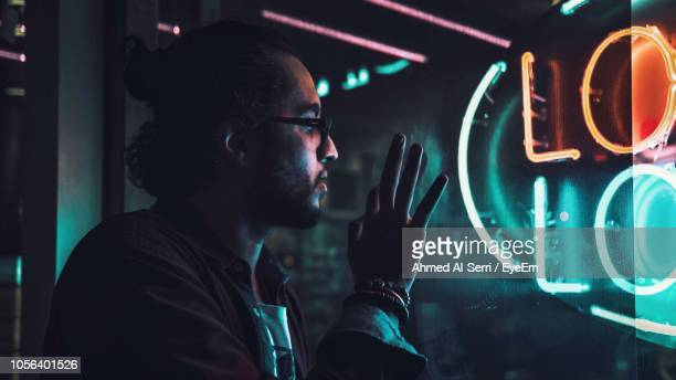 close-up of thoughtful man looking through window at night - jiddah stock pictures, royalty-free photos & images