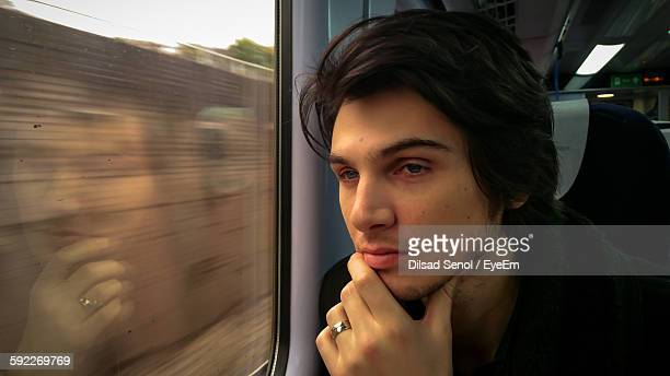 close-up of thoughtful man with hand on chin sitting in train - only young men stock pictures, royalty-free photos & images