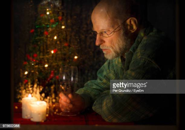 Close-Up Of Thoughtful Senior Man Sitting By Illuminated Christmas Tree At Home