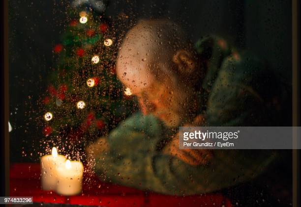 Close-Up Of Thoughtful Senior Man Sitting By Illuminated Christmas Tree Seen Through Window
