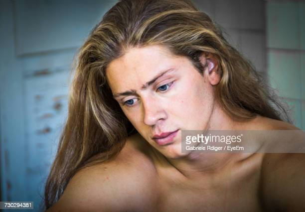 Close-Up Of Thoughtful Shirtless Young Man With Long Blond Hair