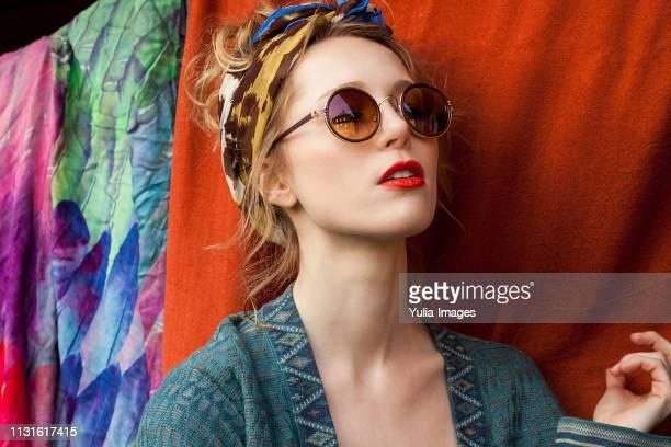 close-up of thoughtful stylish woman wearing sunglasses against fabric - pañuelo de cabeza fotografías e imágenes de stock