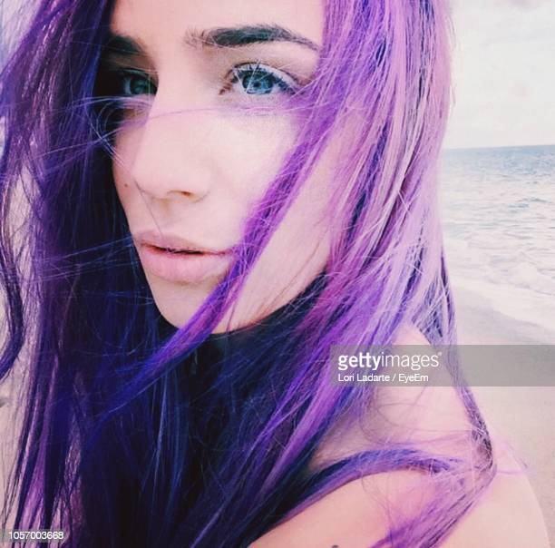 close-up of thoughtful woman with purple hair at beach - purple hair stock photos and pictures