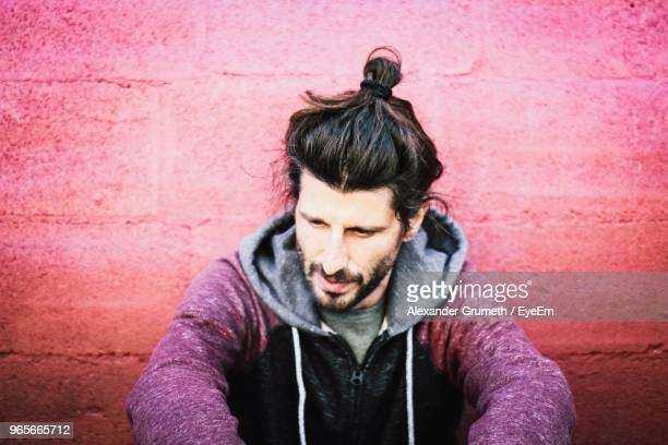 close-up of thoughtful young man sitting by wall - man bun stock pictures, royalty-free photos & images