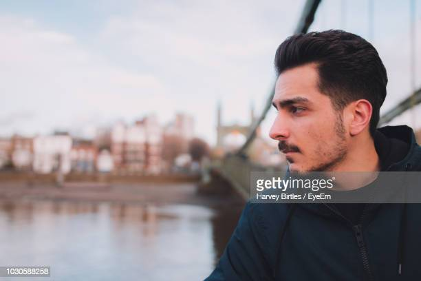 close-up of thoughtful young man standing by river in city - stubble stock pictures, royalty-free photos & images
