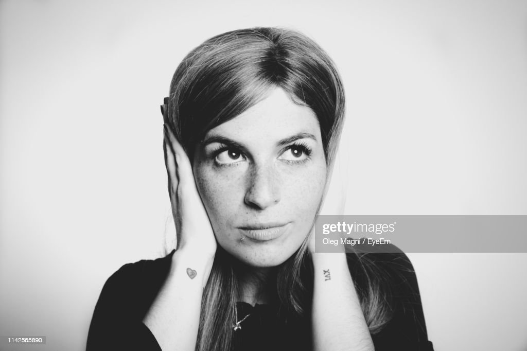 Close-Up Of Thoughtful Young Woman Covering Ears Against White Background : Stock Photo