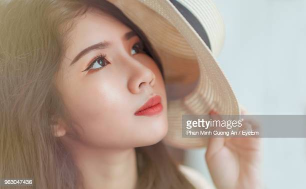 Close-Up Of Thoughtful Young Woman Holding Hat