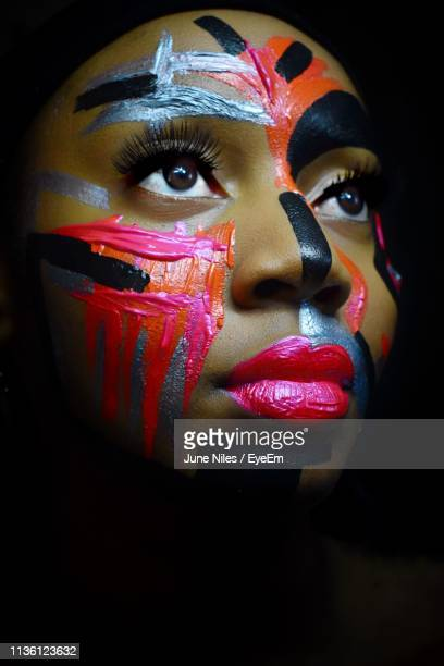 close-up of thoughtful young woman with face paint against black background - body paint stock pictures, royalty-free photos & images