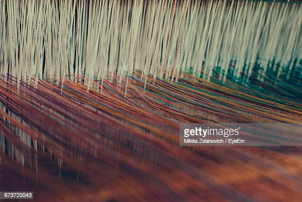 Close-Up Of Threads On Loom In Textile Factory