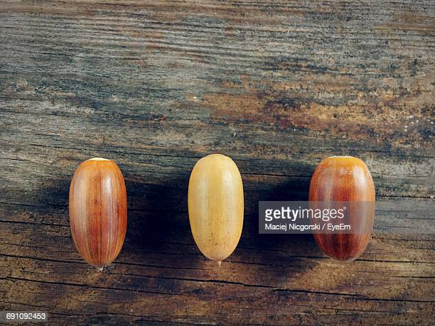 Close-Up Of Three Acorns On Wooden Table