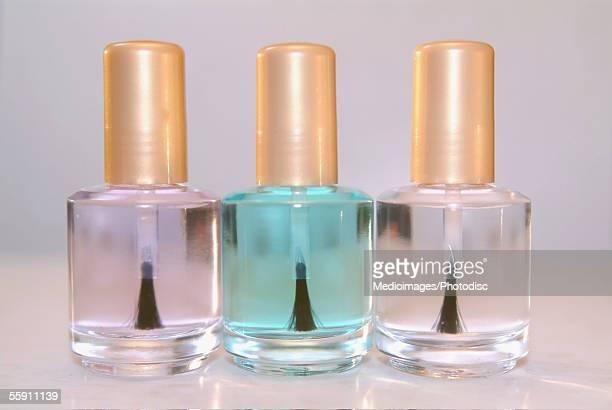 close-up of three bottles of clear nail polish - マニキュア液 ストックフォトと画像