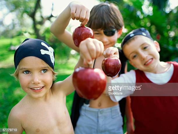 Close-up of three children holding apples