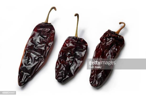 Closeup of three dried guajillo chili peppers on a white background 2013