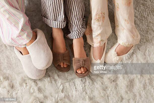 Close-up of three females in slippers